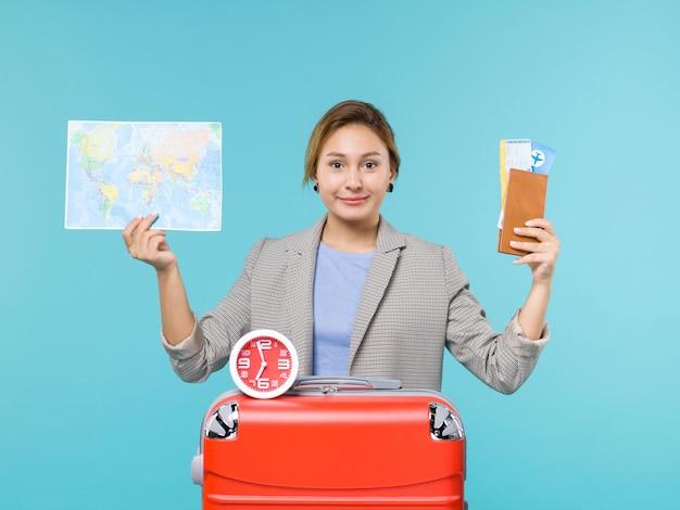 青い背景の航海の旅の海の旅の休暇の地図とチケットを保持している休暇中の女性の正面図