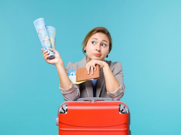 地図の財布と水色の背景の飛行機の航海海の旅行旅行の休暇のチケットを保持している休暇中の女性の正面図