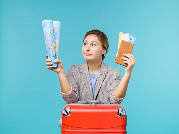 Вид спереди женщина в отпуске, держащая бумажник с картой и билеты на синем фоне, путешествие на самолете, морское путешествие, путешествие, отпуск