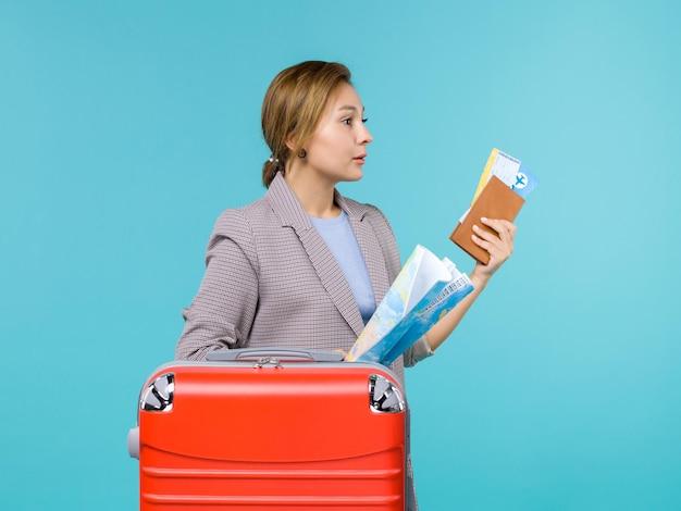 밝은 파란색 배경 비행기 항해 여행 여행 휴가에지도 지갑과 티켓을 들고 휴가에 전면보기 여성