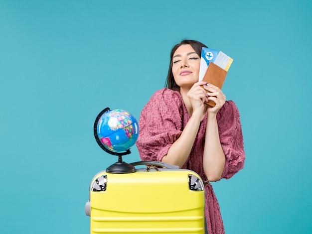 青い背景の海の休暇の女性の旅行の旅の夏に飛行機のチケットを保持している休暇中の女性の正面図