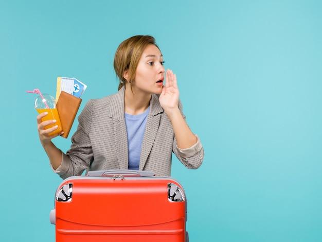 파란색 배경 휴가 비행기 여행 항해 바다 여행에 누군가를 호출하는 휴가 티켓을 들고 전면보기 여성