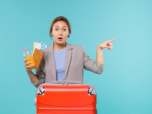Вид спереди женщина в отпуске с билетами на голубом фоне, отпуск на самолете, путешествие, морское путешествие