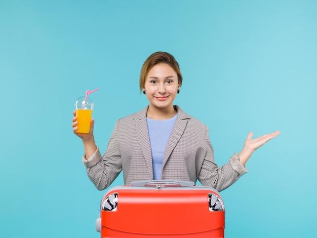 파란색 배경 휴가 비행기 항해 바다 여행 여행에 신선한 주스를 들고 그녀의 빨간 가방과 함께 휴가에 전면보기 여성