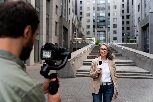 Журналистка, вид спереди, берет интервью