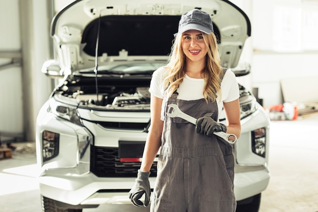 Front view female mechanic holding wrench