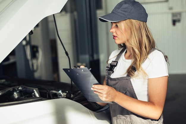 Front view female mechanic inspecting car