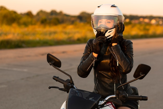 Front view of female motorcycle rider with helmet on