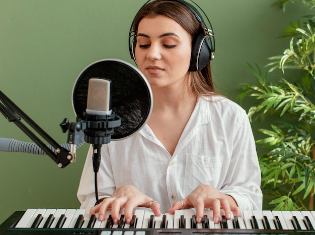 Front view of female musician singing and playing piano keyboard