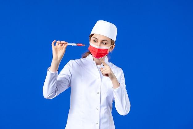 파란색에 그녀의 손에 빨간 마스크와 주사 흰색 의료 소송에서 전면보기 여성 간호사