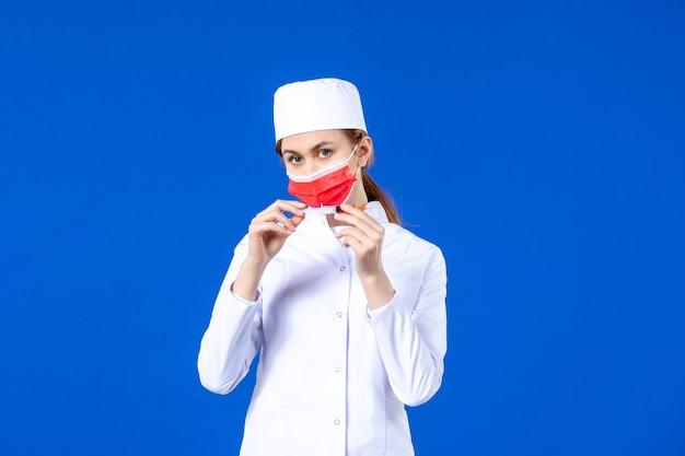 赤いマスクと青い手に注射をした白い医療スーツを着た正面図の女性看護師