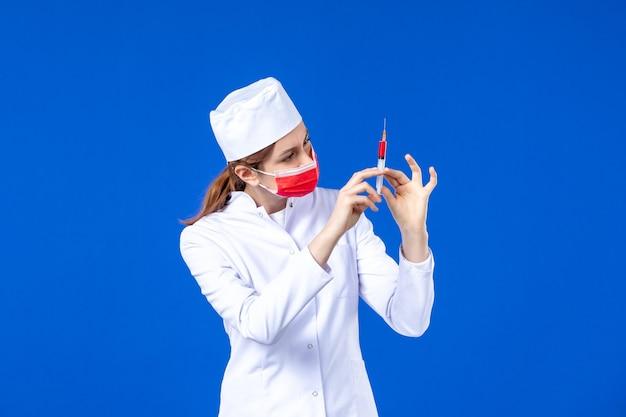 Вид спереди медсестра в белом медицинском костюме с красной маской и инъекцией в руках на синем