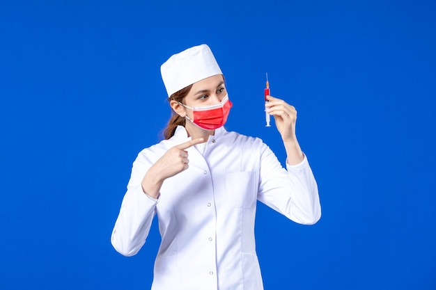 Front view female nurse in white medical suit with red mask and injection in her hands on blue