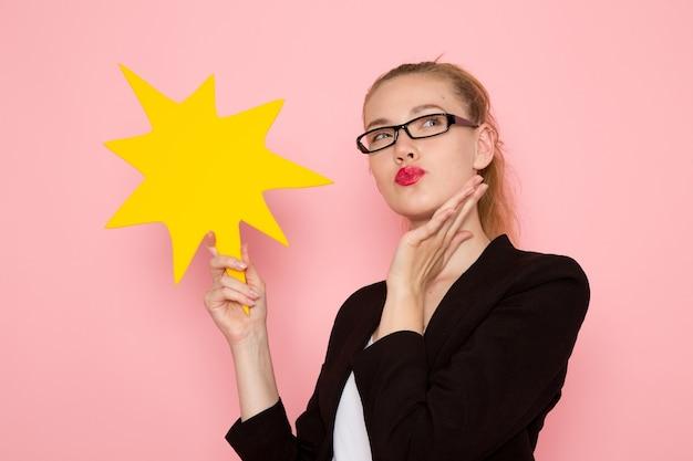 Vista frontale dell'impiegato femminile in giacca rigorosa nera che tiene grande cartello giallo pensando sulla parete rosa