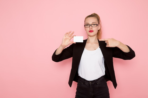Front view of female office worker in black strict jacket holding card on light-pink wall