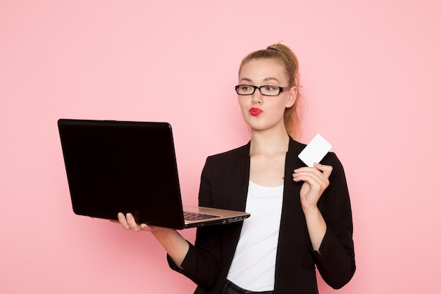 Front view of female office worker in black strict jacket holding card and using laptop on pink wall
