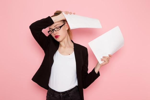 Vista frontale dell'impiegato femminile in giacca rigorosa nera che tiene documenti diversi sulla parete rosa chiaro