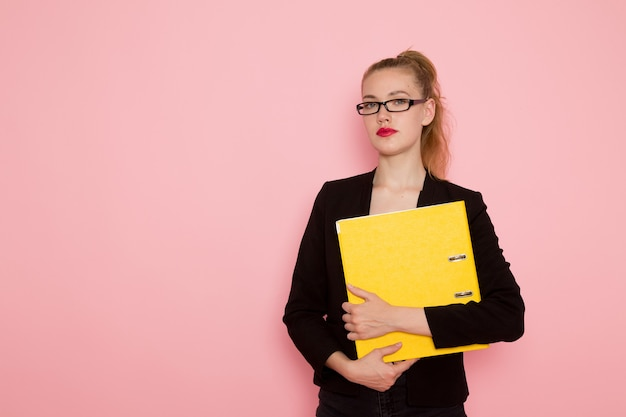 Front view of female office worker in black strict jacket holding documents on light-pink wall