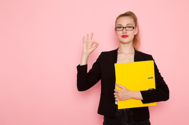Vista frontale dell'impiegato femminile in giacca rigorosa nera che tiene i documenti sulla parete rosa chiaro