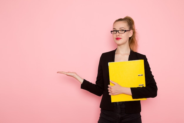 Front view of female office worker in black strict jacket holding documents on pink wall