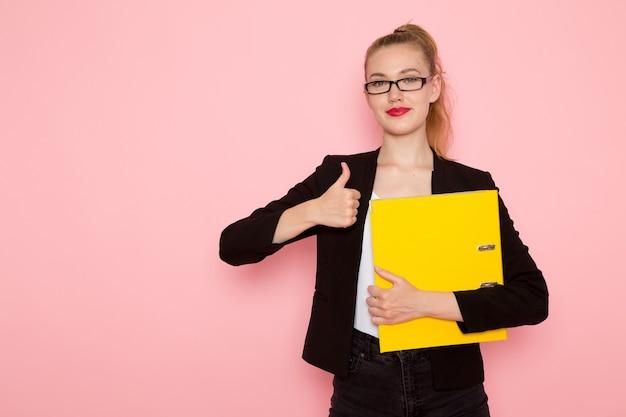 Vista frontale dell'impiegato femminile in giacca rigorosa nera che tiene i documenti e sorridente sulla parete rosa chiaro
