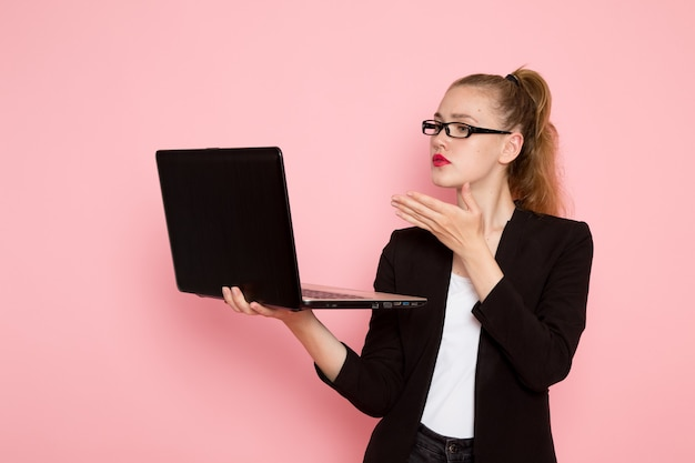 Front view of female office worker in black strict jacket holding her laptop on light-pink wall