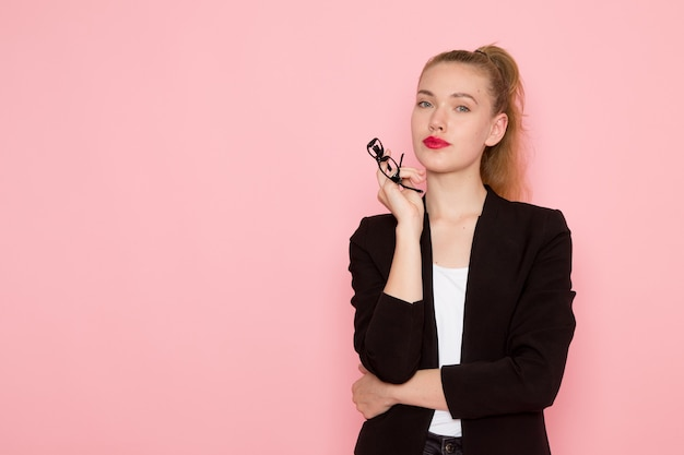 Front view of female office worker in black strict jacket holding her optical sunglasses on light-pink wall
