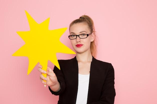 Vista frontale dell'impiegato femminile in giacca rigorosa nera che tiene un enorme cartello giallo sulla parete rosa