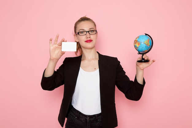 Front view of female office worker in black strict jacket holding little globe and card on light-pink wall