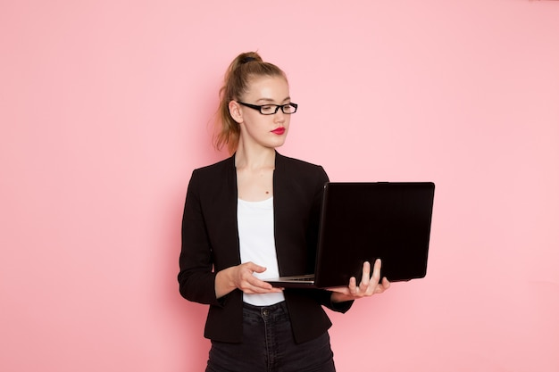 Front view of female office worker in black strict jacket holding and using her laptop on light-pink wall