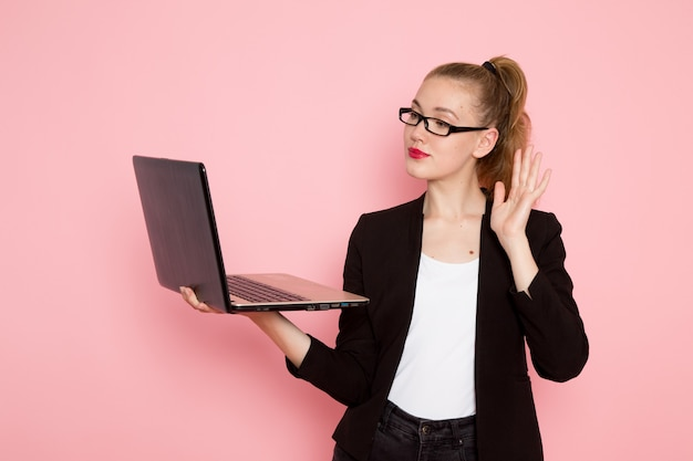 Front view of female office worker in black strict jacket holding and using her laptop on pink wall
