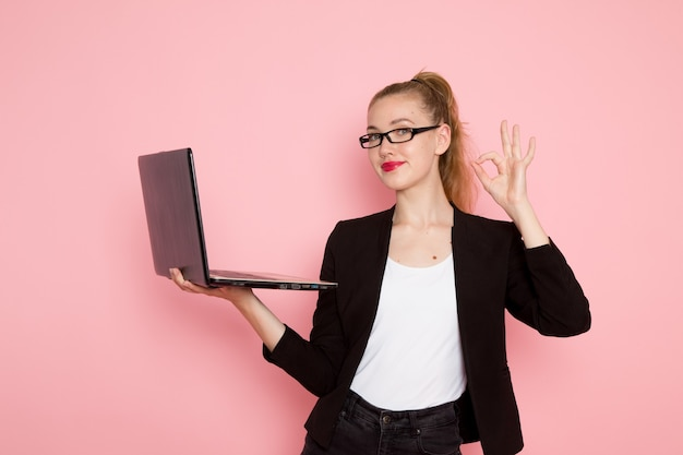 Front view of female office worker in black strict jacket holding and using laptop on the light-pink wall