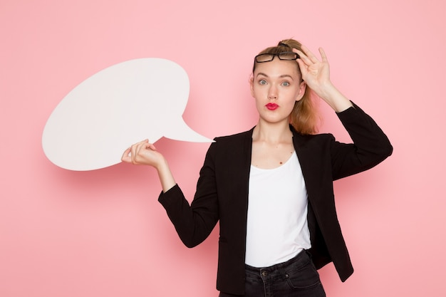 Vista frontale dell'impiegato femminile in giacca rigorosa nera con cartello bianco sulla parete rosa chiaro
