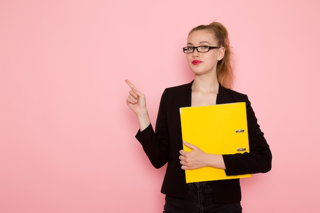 Front view of female office worker in black strict jacket holding yellow document on pink wall