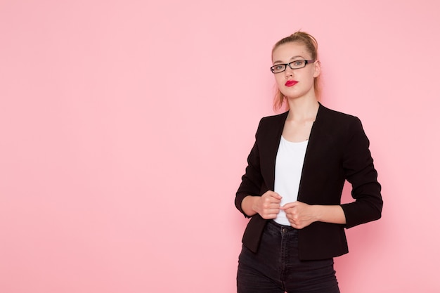 Front view of female office worker in black strict jacket just posing on the pink wall