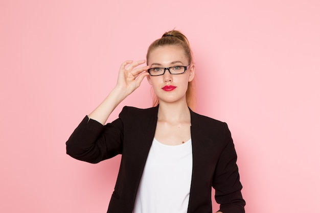 Front view of female office worker in black strict jacket posing touching her sunglasses on light-pink wall