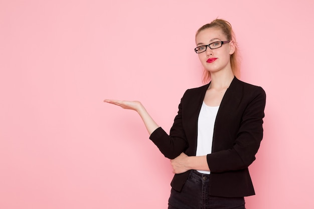 Front view of female office worker in black strict jacket raising her hand on light-pink wall
