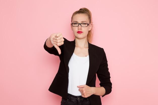 Vista frontale dell'impiegato femminile in rivestimento rigoroso nero che mostra a differenza del segno sulla parete rosa-chiaro