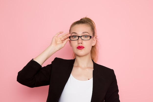Front view of female office worker in black strict jacket wearing optical sunglasses on pink wall