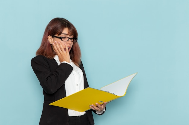 파란색 표면에 문서를 들고 전면보기 여성 회사원