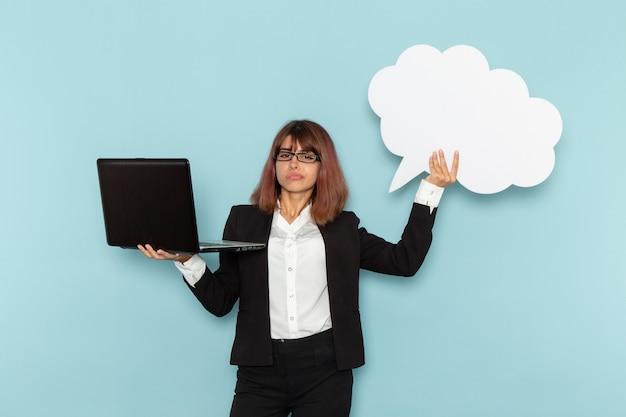 Impiegato di ufficio femminile di vista frontale che tiene grande segno bianco e computer portatile sulla superficie blu