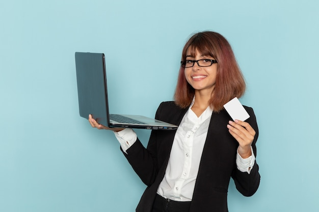 Front view female office worker holding card and laptop on the blue surface