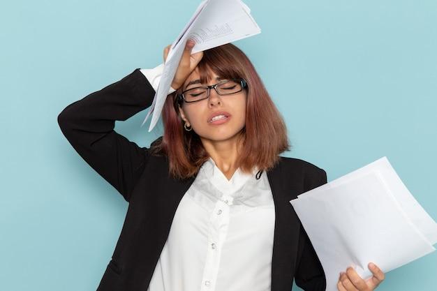 Impiegato di ufficio femminile di vista frontale che tiene lavoro di ufficio differente sulla superficie blu