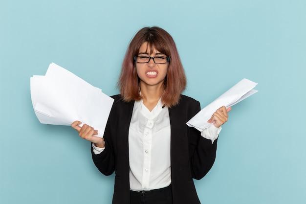 밝은 파란색 표면에 다른 서류를 들고 전면보기 여성 회사원
