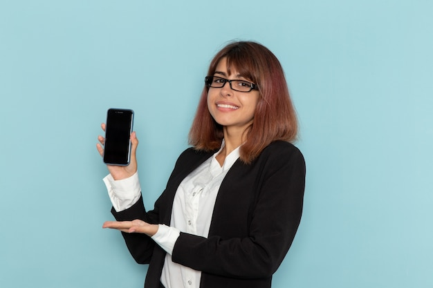 Front view female office worker holding her smartphone on blue surface