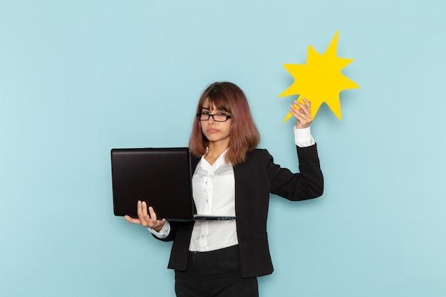 Impiegato di ufficio femminile di vista frontale che tiene il segno ed il computer portatile gialli enormi sulla superficie blu