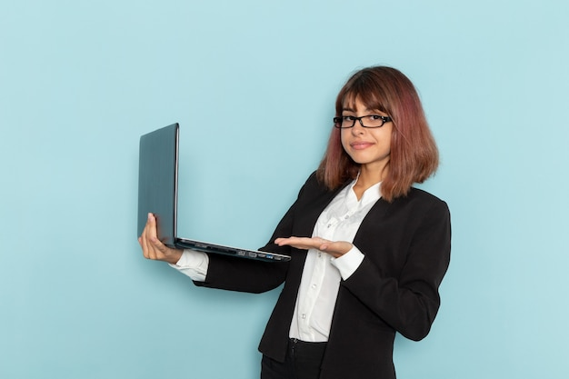 Front view female office worker holding laptop and smiling on the blue surface