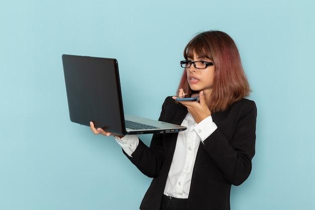 Vista frontale femminile impiegato in possesso di laptop mentre si parla al telefono sulla superficie blu