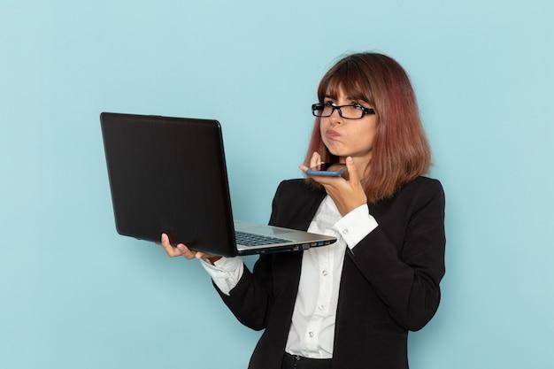 Vista frontale femminile impiegato in possesso di telefono e computer portatile sulla superficie blu