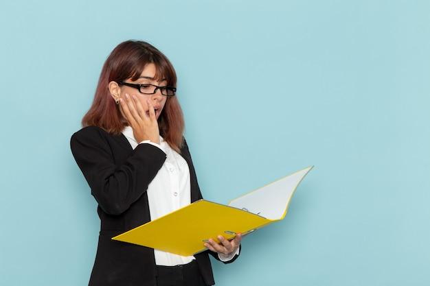 Vista frontale femminile impiegato in possesso e lettura del documento sulla superficie blu